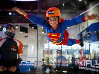 Boy worn like a superman playing in a skydiving simulator